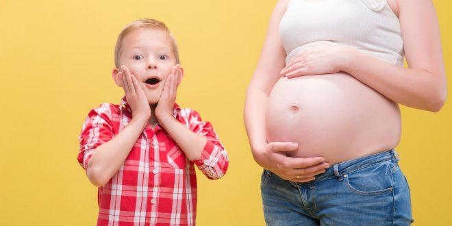 صورة لطفل يفاجأ بحجم بطن أمه