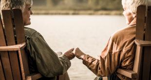 صورة عجوزين يمسكان بيد بعضهما البعض