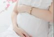 woman-in-soft-white-dress-sits-and-holds-her-pregnant-belly